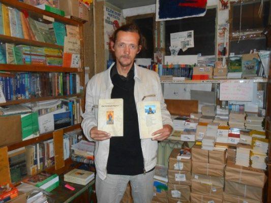 Александр Волощук со своими книгами, созданными после путешествий