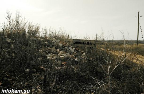 Груды битого кирпича и бетонные плиты заросли травой